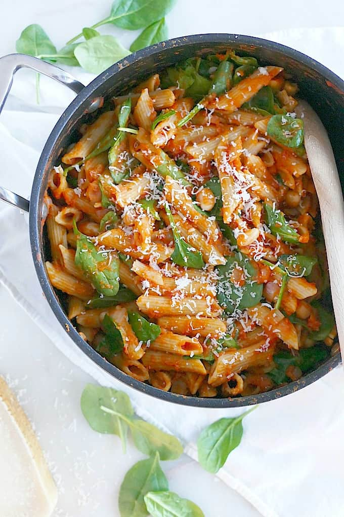 Pasta with sauce and spinach in a pot