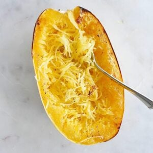 half of a Spaghetti Squash with a fork in it on a counter