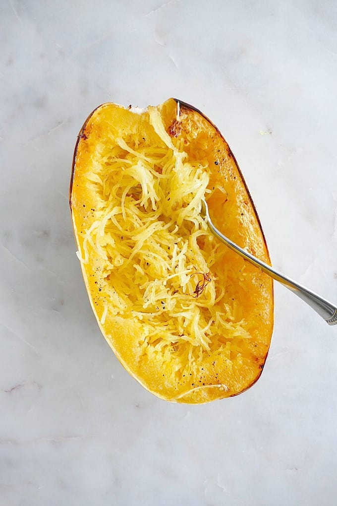 one half of cooked spaghetti squash with a fork inserted into the the noodles