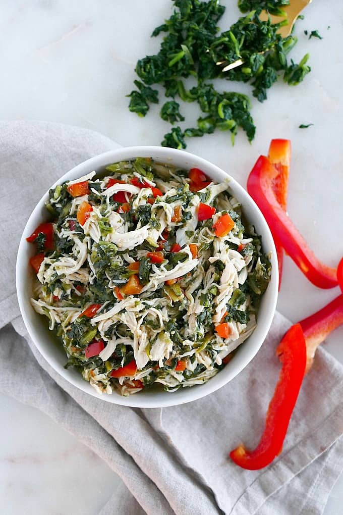 Slow Cooker Mexican shredded Chicken with spinach and bell peppers in a white bowl