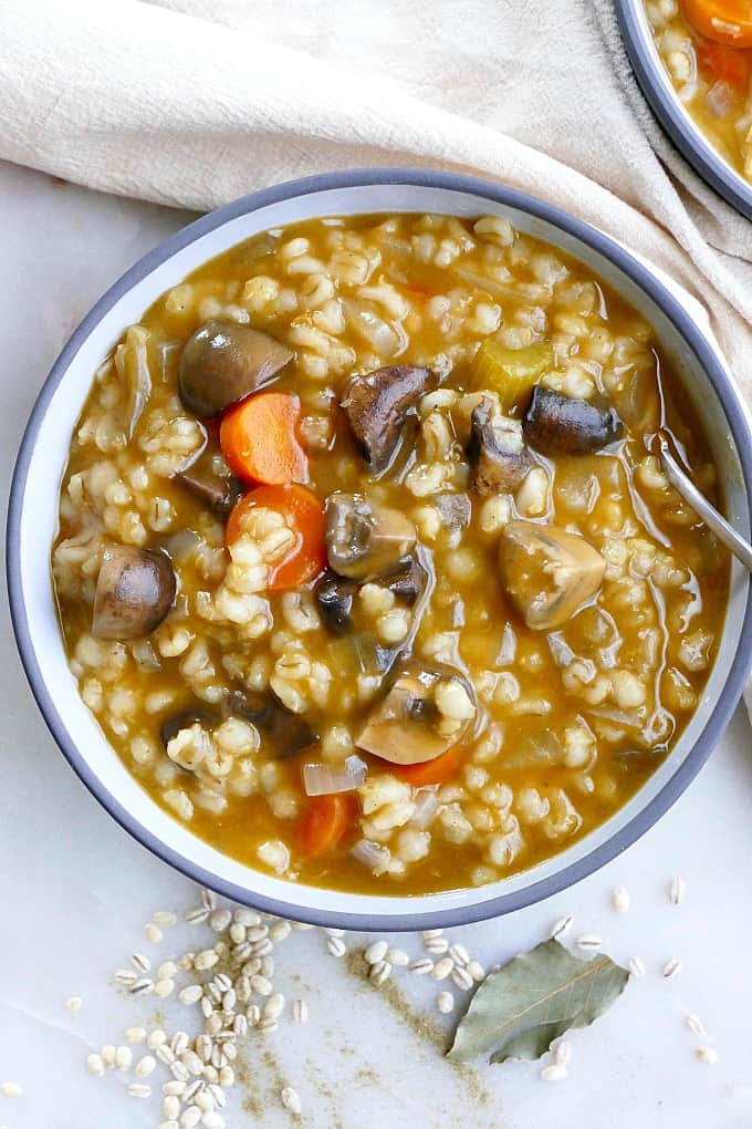Mushroom Barley Stew in a grey bowl with a spoon and white napkin