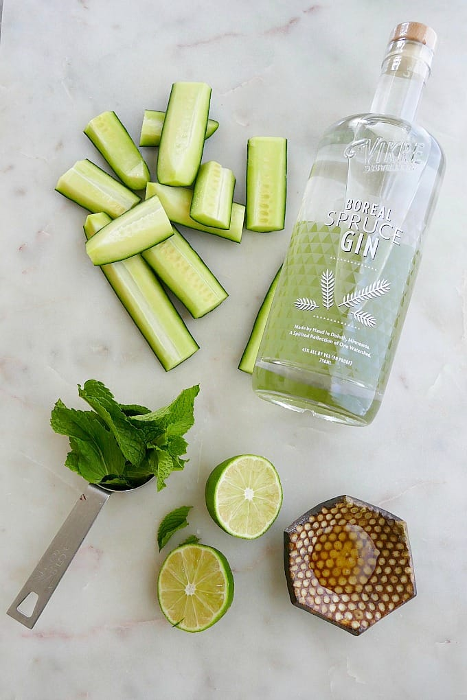 sliced cucumber, bottle of gin, mint leaves, lime, and honey spread out on a counter