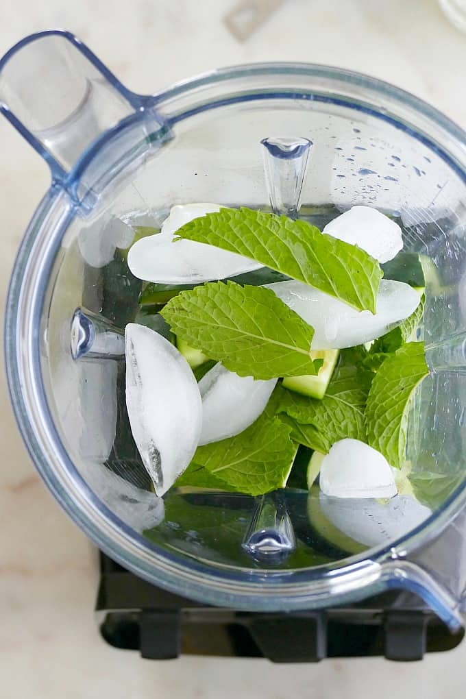 ingredients for a cocktail in a blender with ice and mint leaves