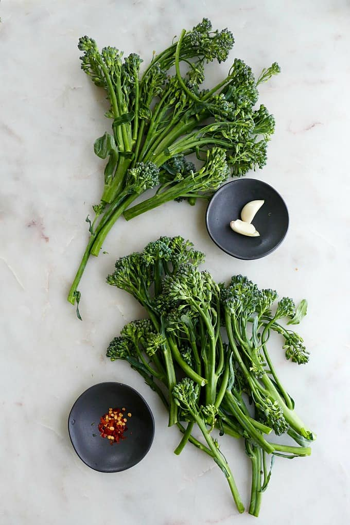 two bunches of broccolini spread out on a counter next to garlic and red pepper