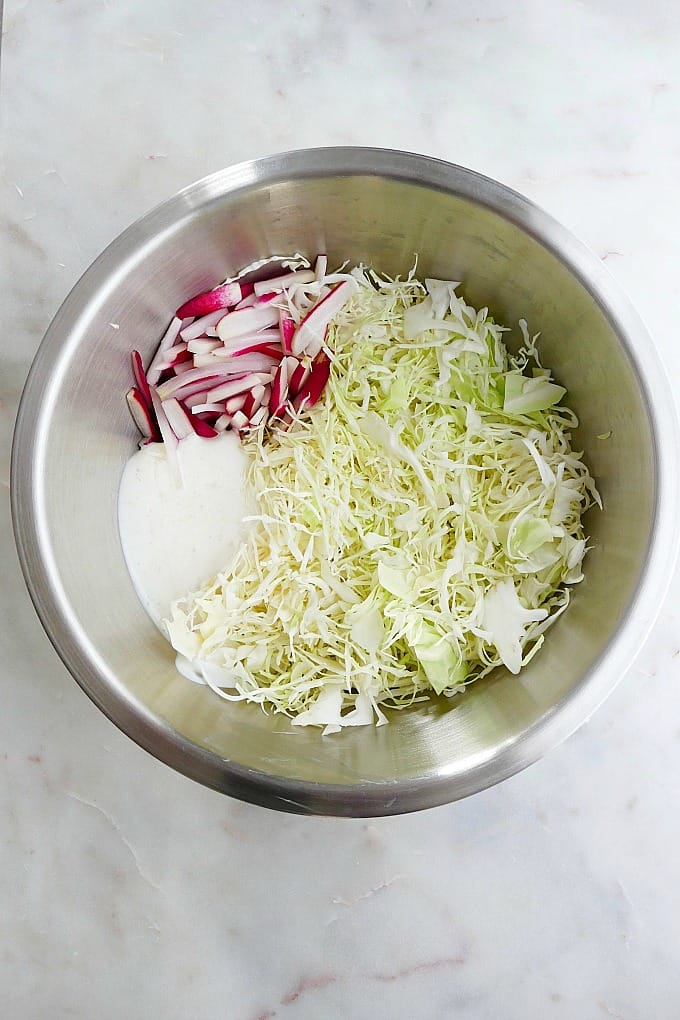 ingredients for coleslaw in a silver mixing bowl on a counter