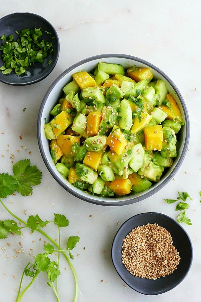 mango cucumber salad in a bowl on the counter next to sesame seeds and cilantro