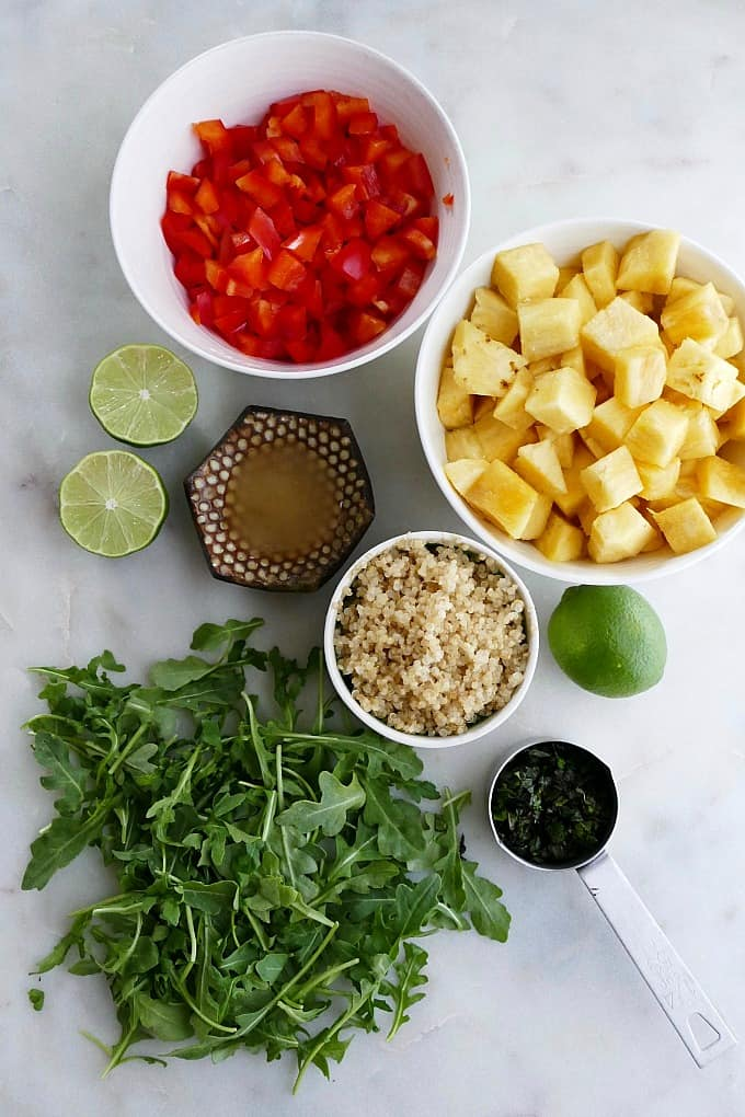 bell pepper, pineapple, quinoa, arugula, lime, mint, and honey on a counter