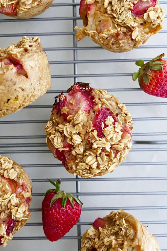 1 strawberry rhubarb oat muffin on a metal cooling rack surrounded by others