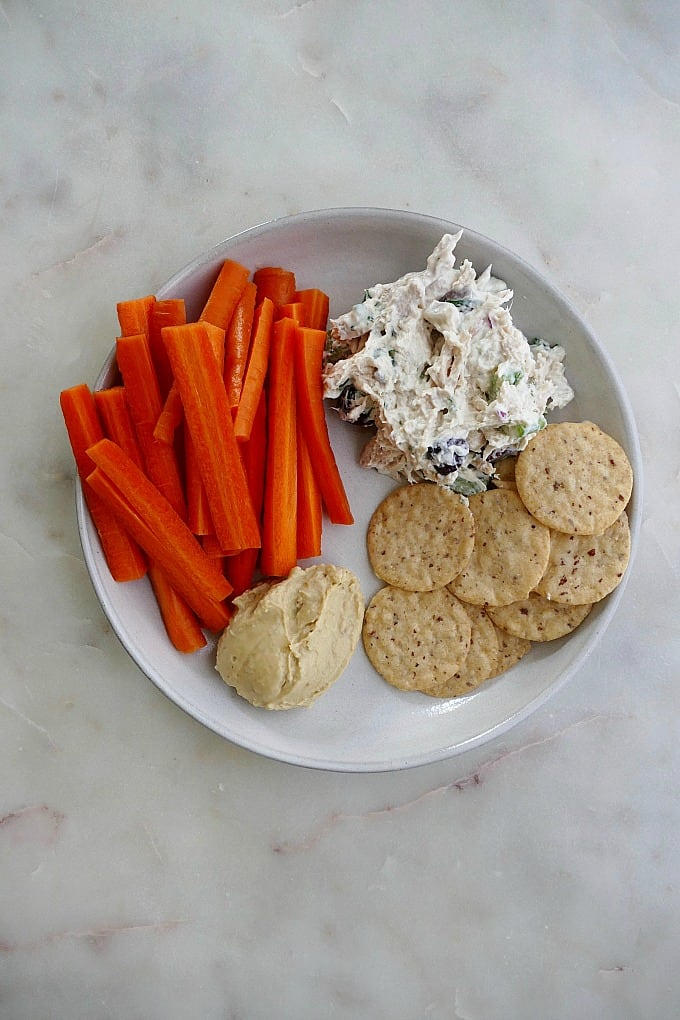 plate with carrots, chicken salad, hummus, crackers