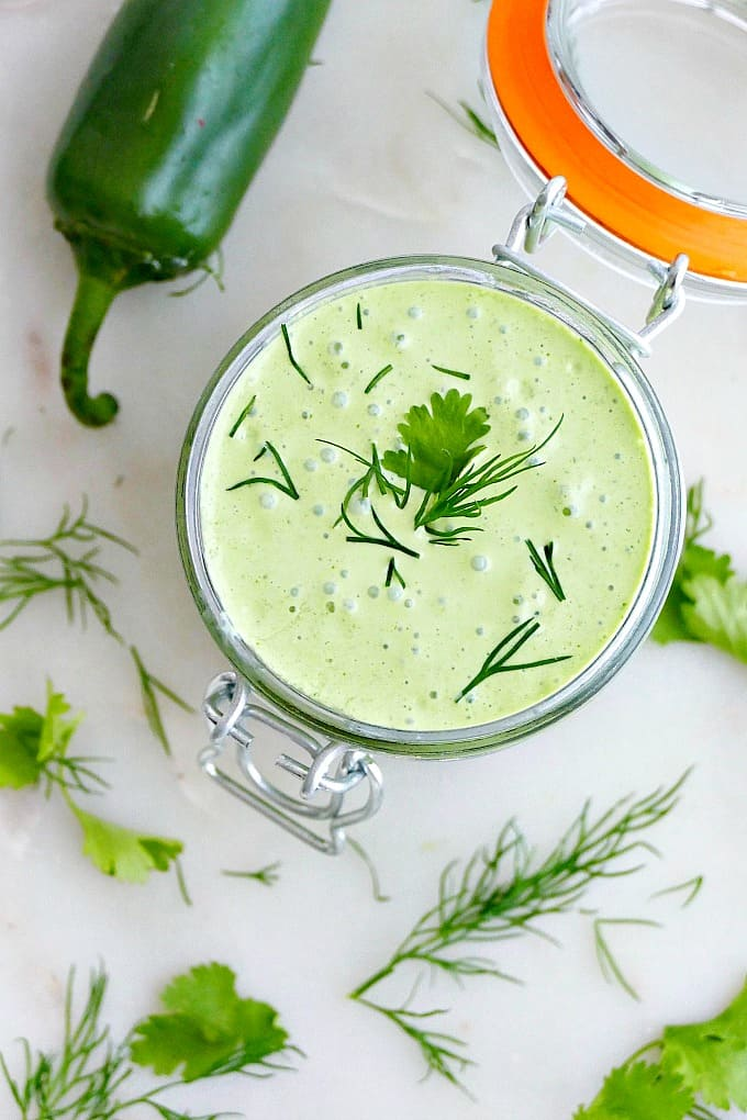 creamy green jalapeno sauce topped with fresh herbs in a container on a counter