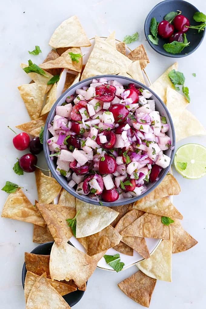 jicama cherry salsa in a serving bowl in the middle of a platter with chips, herbs, and fresh lime