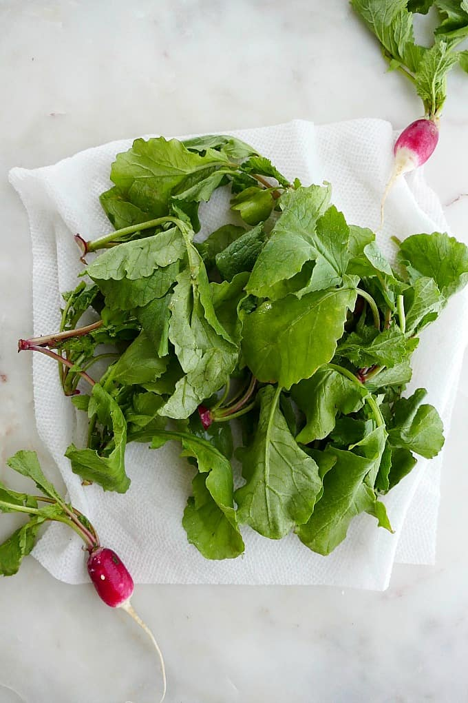 radish leaves on a damp paper towel on a counter next to full radishes