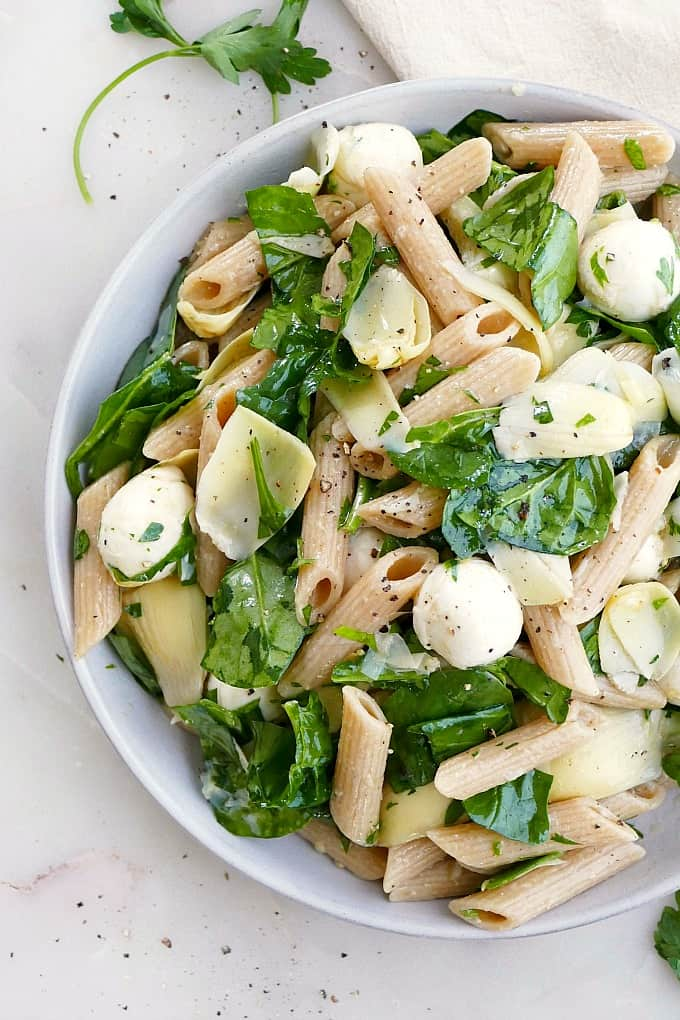 pasta salad with spinach, artichoke, and mozzarella on a platter