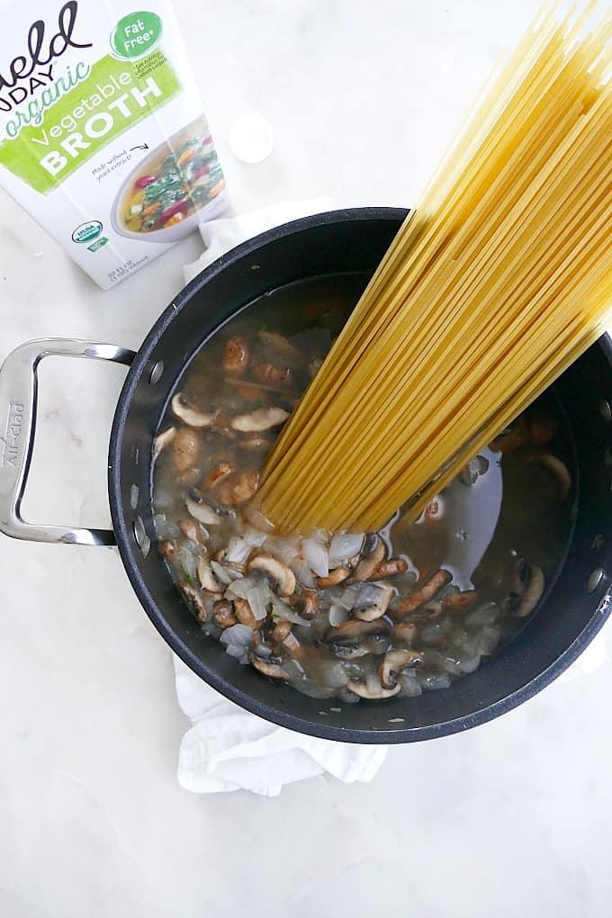sauteed mushroom and onions, broth, and spaghetti n a black pot