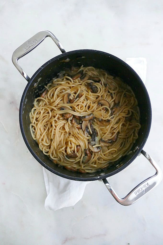 cooked spaghetti with mushrooms in a black pot on a white towel