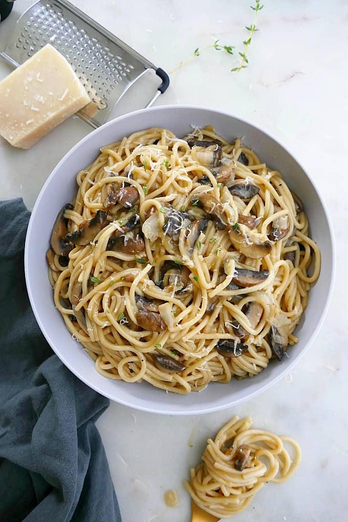 mushroom spaghetti in a blue bowl next to a blue napkin