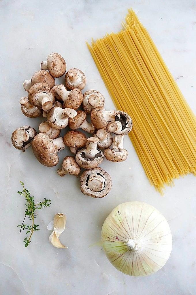 mushrooms, spaghetti, onion, garlic, thyme on a white countertop