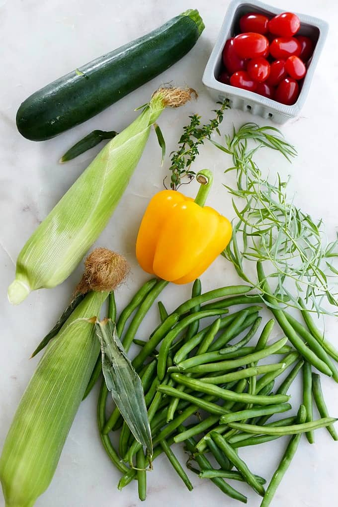 zucchini, corn, bell pepper, green beans, tarragon, tomatoes, and herbs on a counter