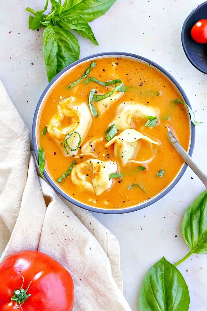 fresh tomato tortellini soup in a blue soup bowl with basil chiffonade