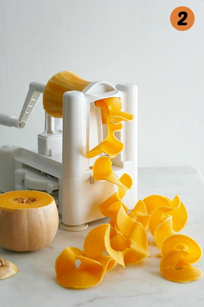 butternut squash in a spiralizer on a white marble countertop