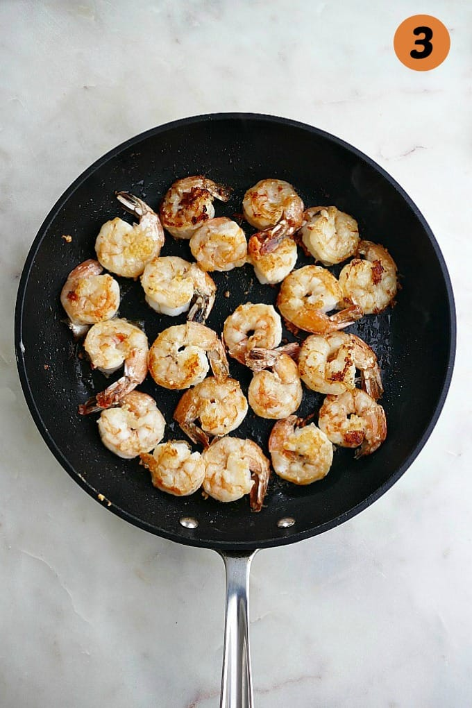 shrimp sauteed in garlic and butter in a black skillet on white countertop