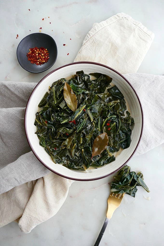 collard greens in white bowl with pepper flakes and fork on white counter