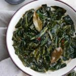 vegan collard greens in a white bowl topped with bay leaves