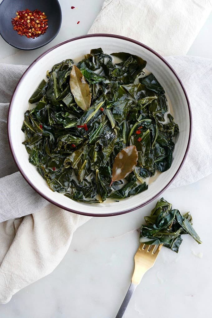 vegan collard greens in a white bowl with gold fork next to it