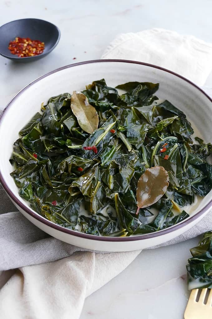 angled shot of vegan collard greens in a white bowl