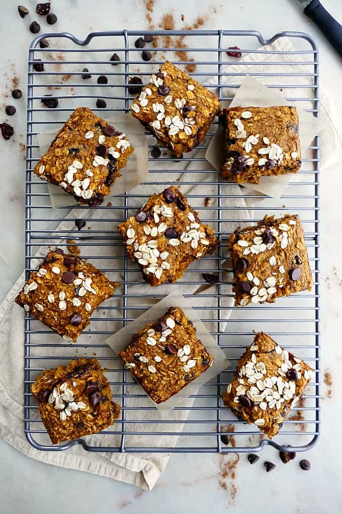 nine pumpkin oatmeal bars on a wire cooling rack on top of a counter