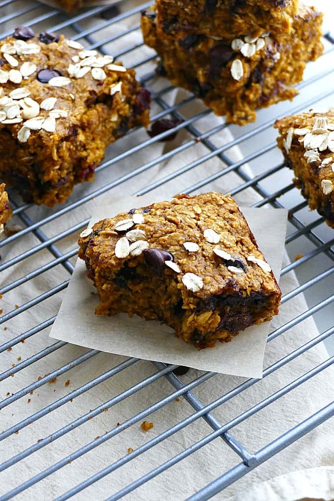 one pumpkin oatmeal bar on a square of parchment paper on a cooling rack