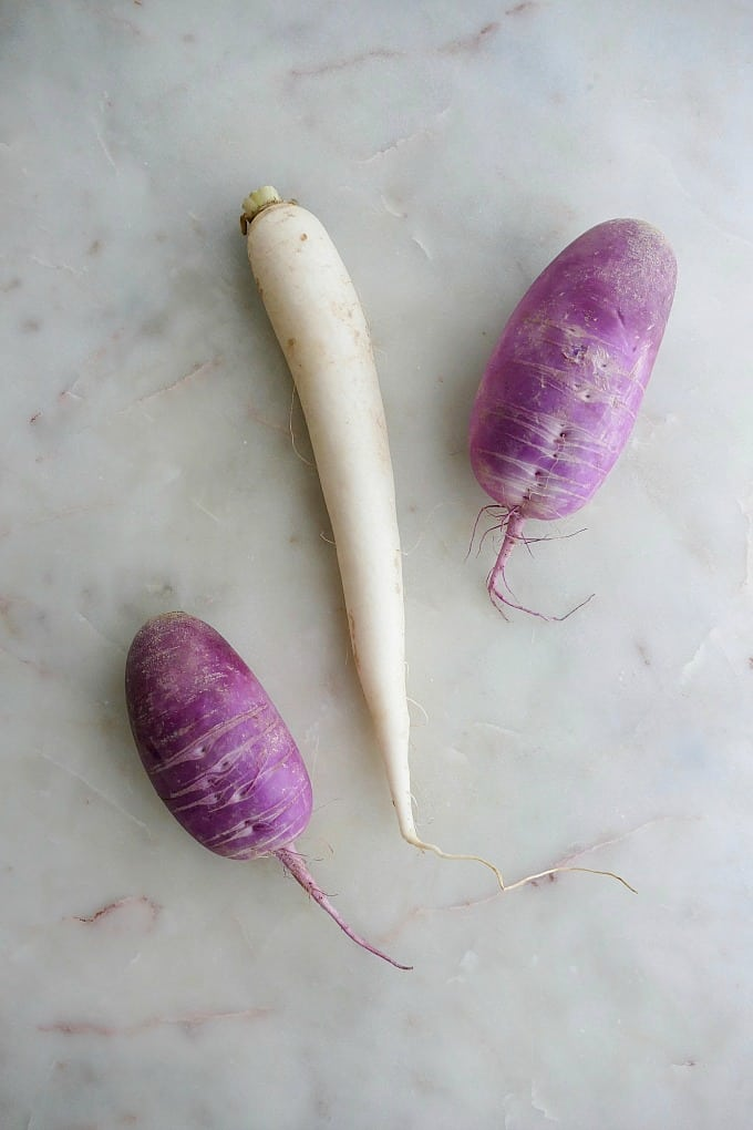white and purple daikon radishes on a white marble countertop