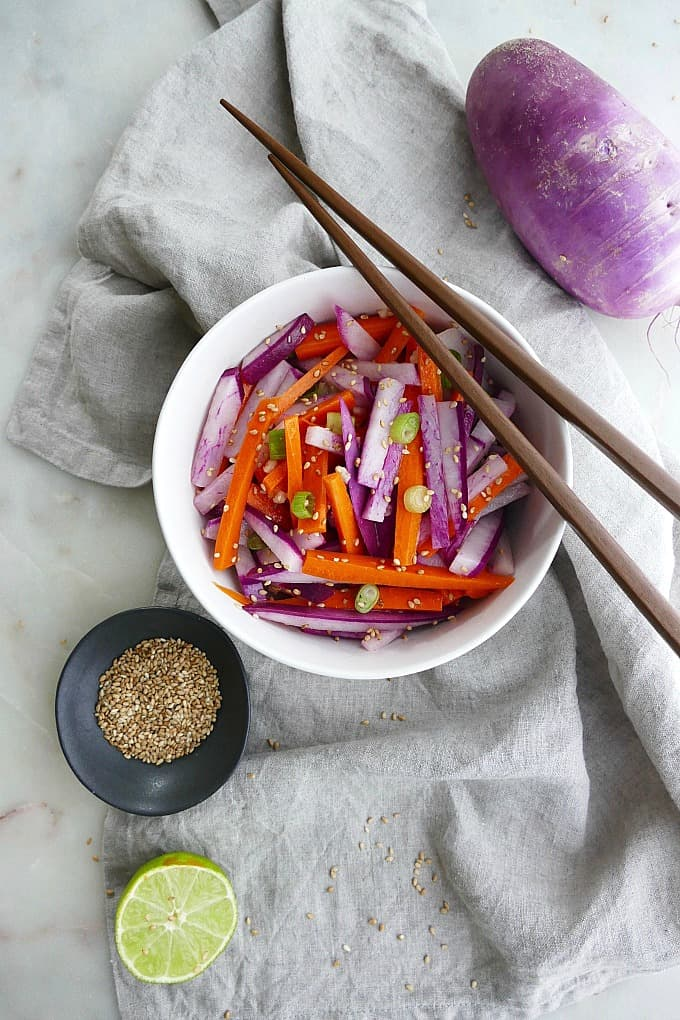 purple radish salad with carrots and green onions in a white bowl on top of a grey napkin with brown chopsticks on the top of the bowl