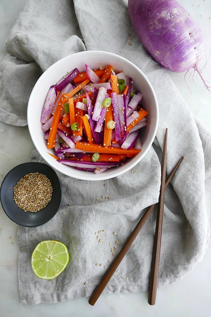 purple radish salad with carrots and green onions in a white bowl on top of a grey napkin next to brown chopsticks, sesame seeds, a purple radish, and a lime