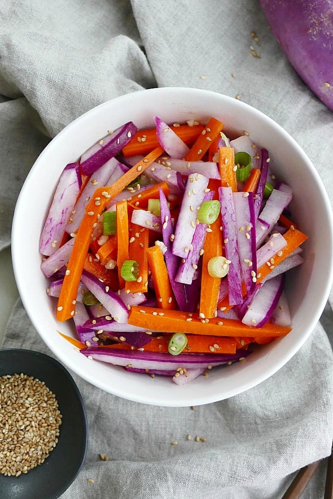 purple radish salad with carrots and green onions in a white bowl on top of a grey napkin