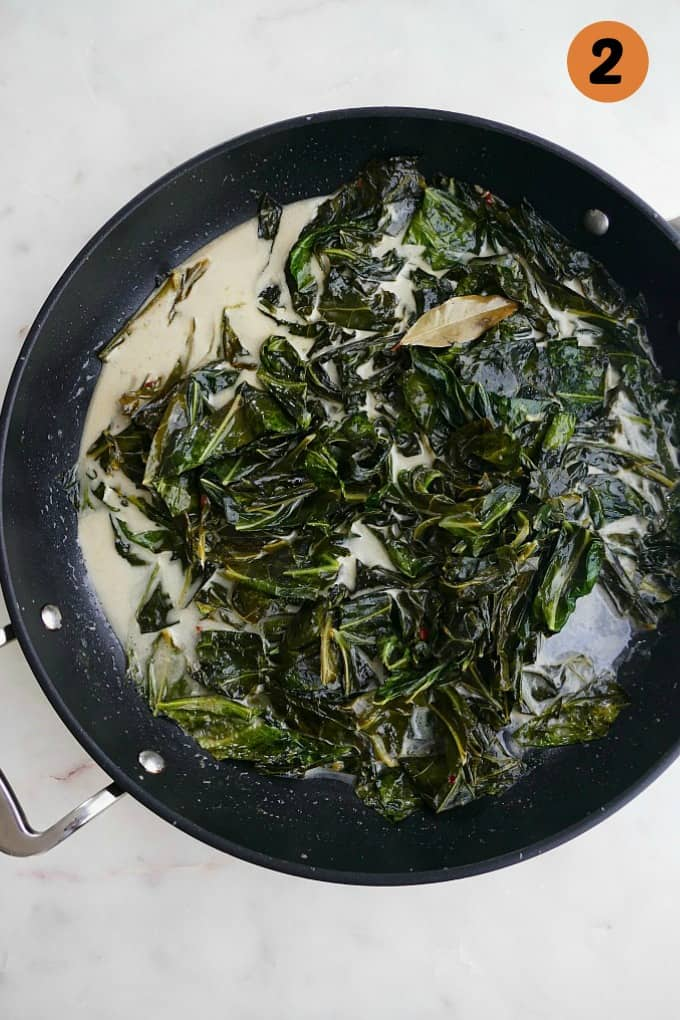 collard greens during the cooking process in a black skillet with coconut milk