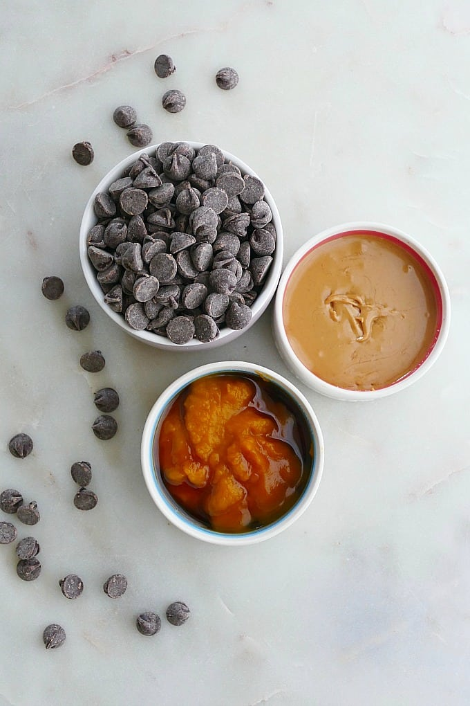 chocolate chips, peanut butter, and pumpkin in small bowls on countertop
