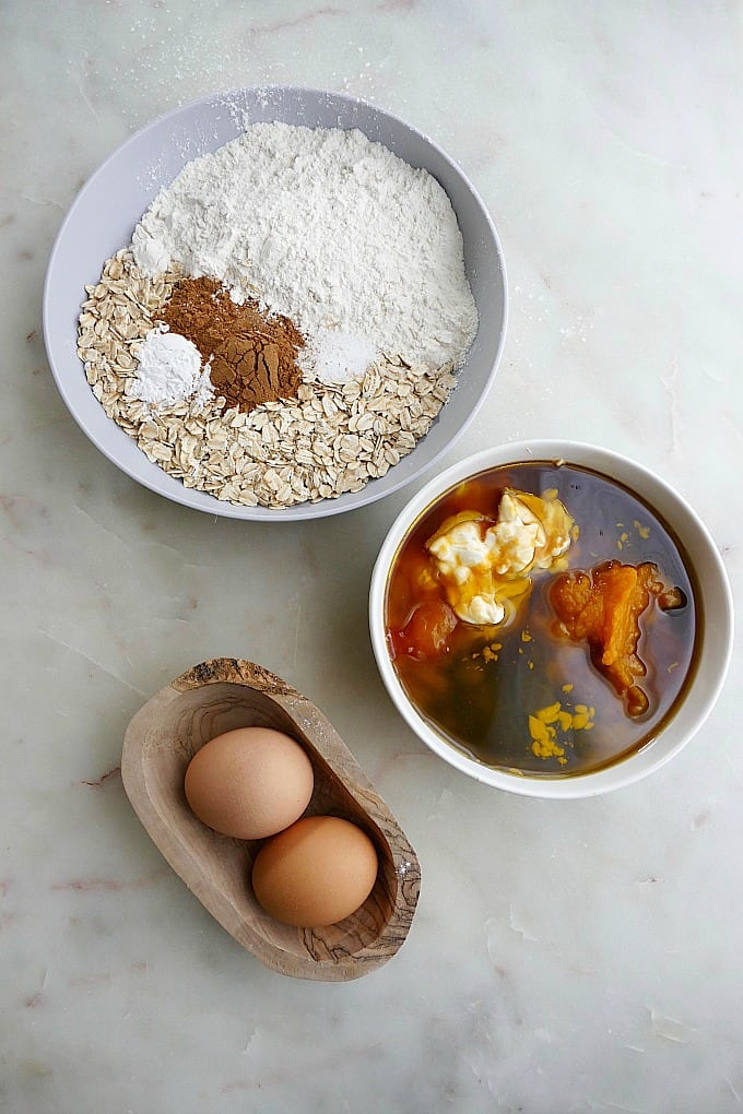 oats, flour, and spices in a bowl next to bowls with wet ingredients and eggs