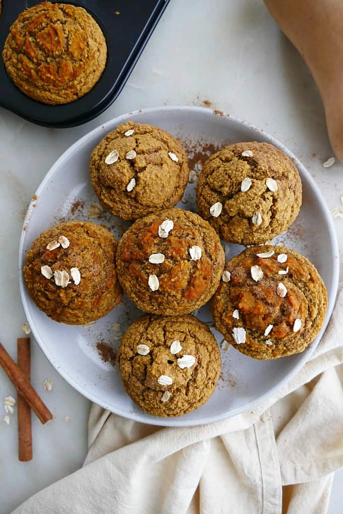 7 butternut squash muffins on a white plate with oats and cinnamon on top
