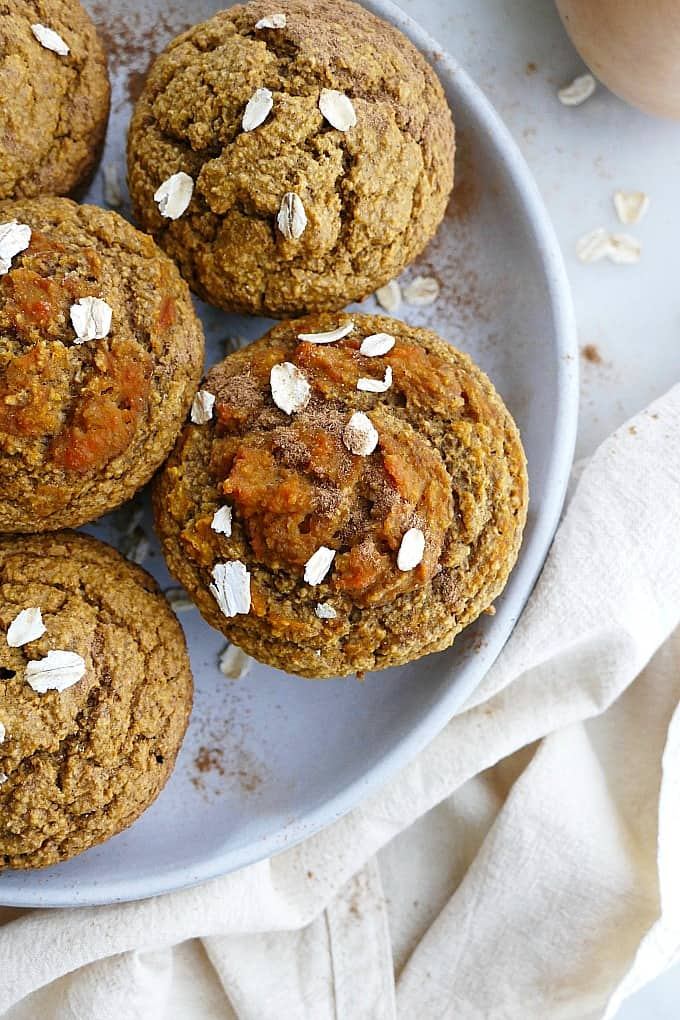 close up of butternut squash muffins on a plate with oats and cinnamon