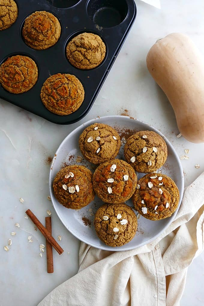 6 butternut squash muffins sprinkled with oats on a serving plate on a counter
