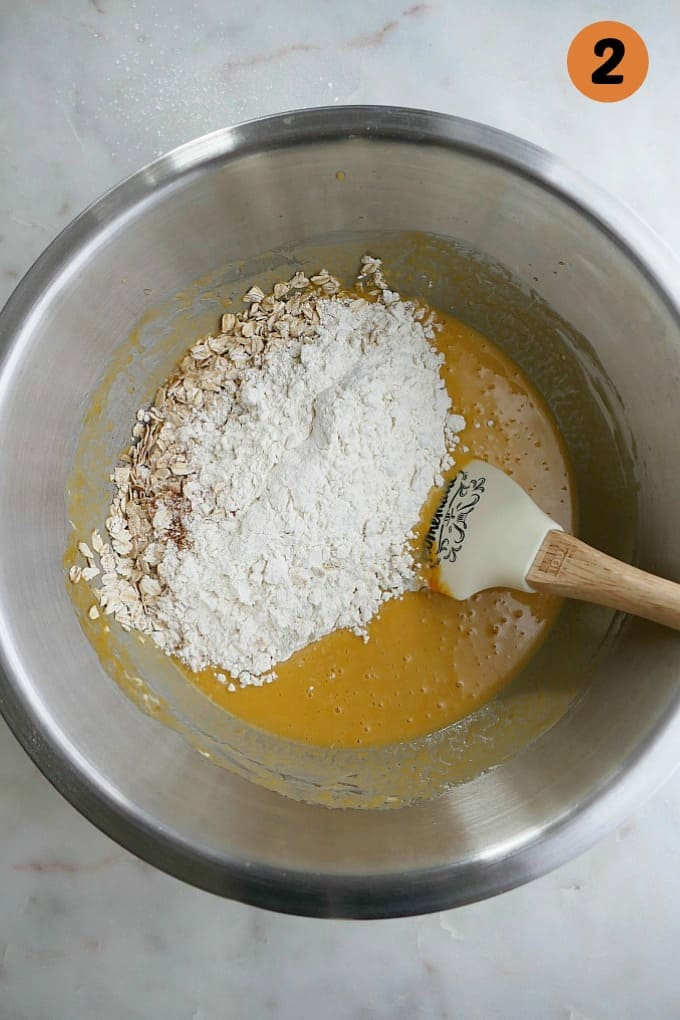 wet ingredients with flour and oats on top in a mixing bowl