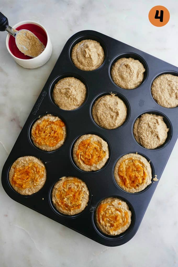 cupcake tin filled with butternut squash muffin batter next to a bowl with a scooper