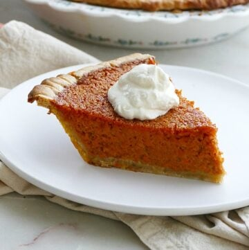 side view of a slice of carrot pie with a dollop of whipped cream