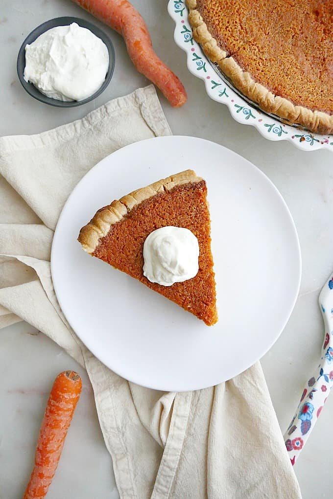 slice of carrot pie with whipped cream on a white plate