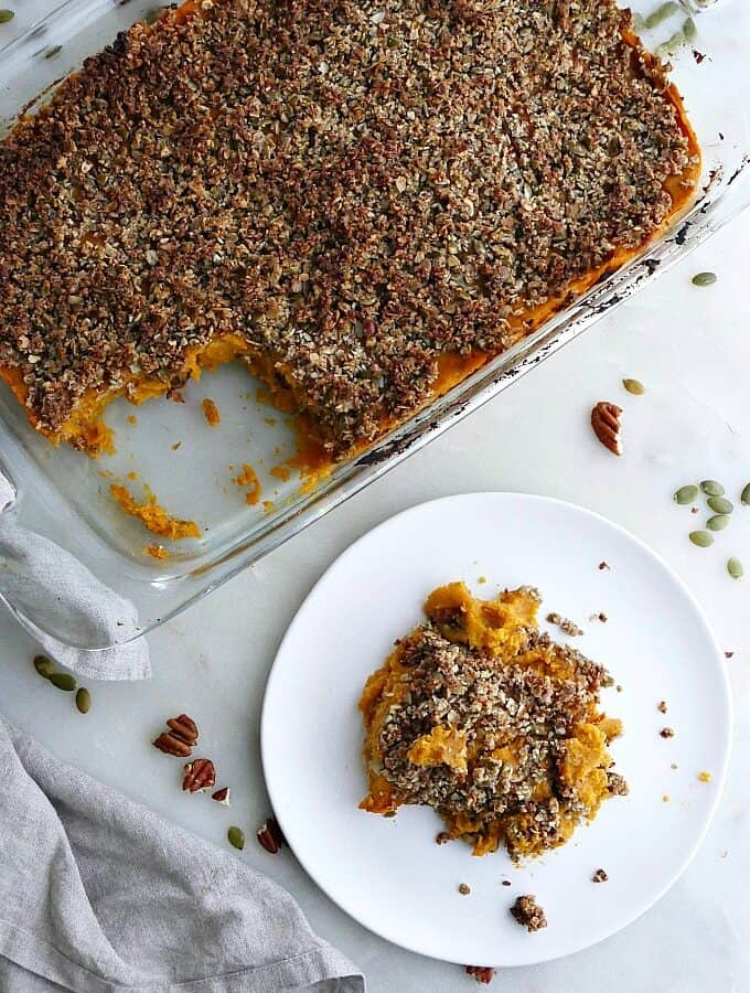 dish with gluten free sweet potato casserole next to a plate with a serving of it