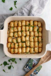 healthy tater tot casserole in a baking dish on a gray napkin on countertop