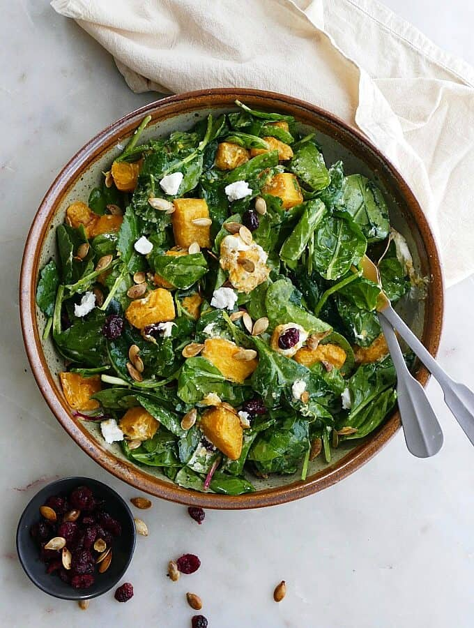 pumpkin salad in a large bowl with silver utensils on top of a yellow napkin