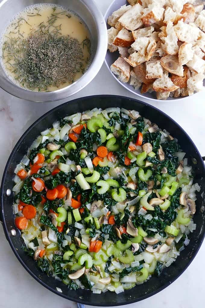 cooked veggies in a black skillet next to a bowl of bread cubes and another mixing bowl