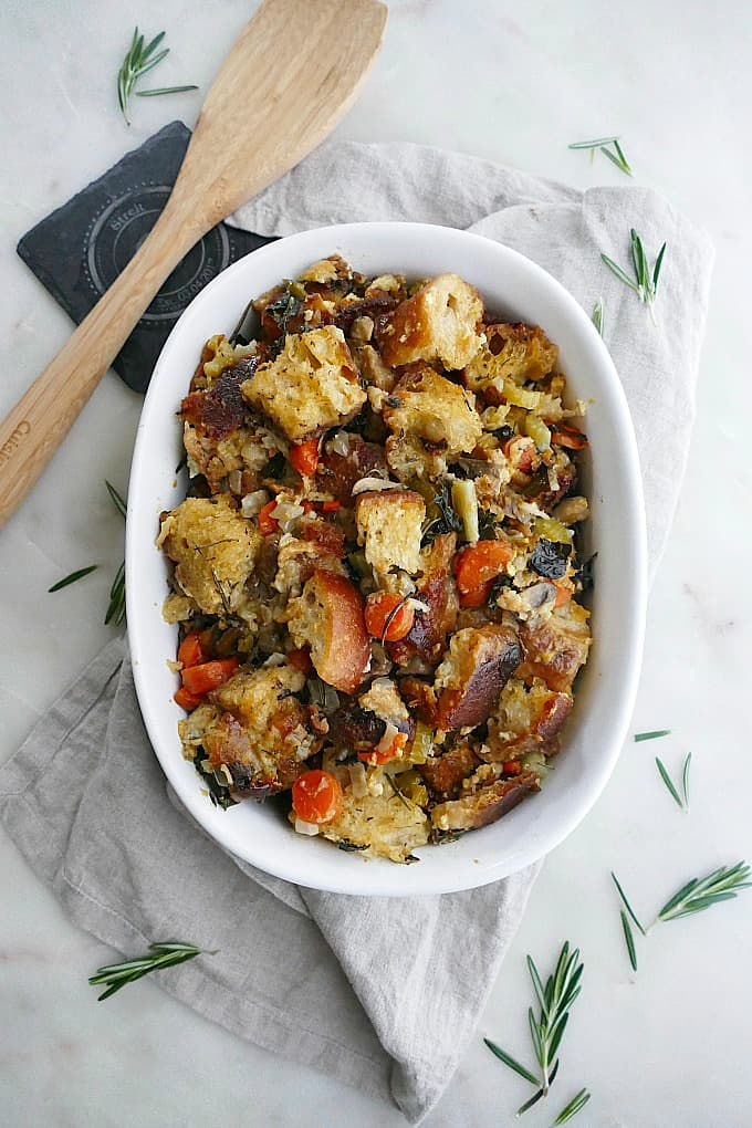 vegetable sourdough stuffing in a white oval baking dish on a counter
